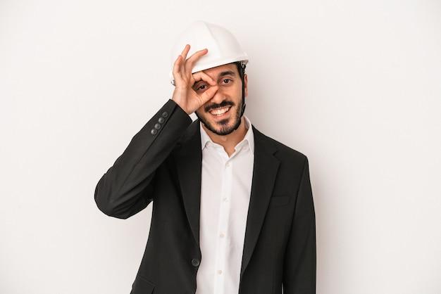白い背景で隔離の建設用ヘルメットを身に着けている若い建築家の男は、目に大丈夫なジェスチャーを維持して興奮しました。