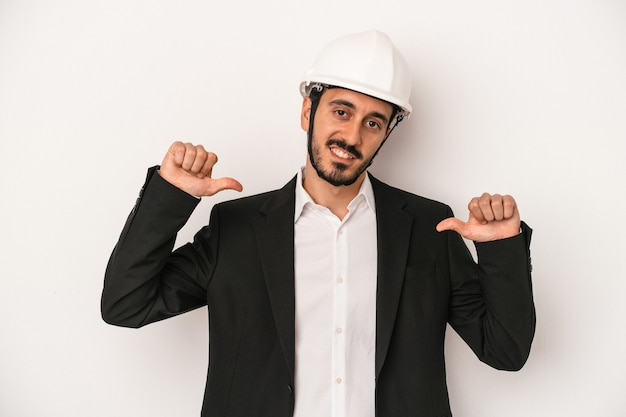 白い背景に分離された建設用ヘルメットを身に着けている若い建築家の男性は、誇りと自信を持って、従うべき例を感じます。