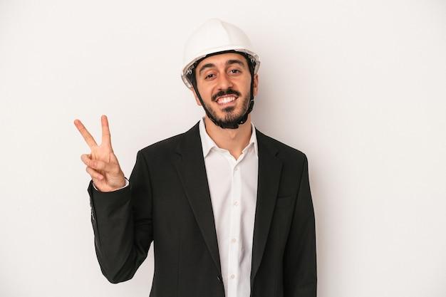 指で平和のシンボルを示す、楽しくてのんきな白い背景に分離された建設用ヘルメットを身に着けている若い建築家の男。