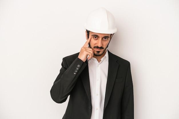 指で寺院を指して、白い背景で隔離の建設用ヘルメットを身に着けている若い建築家の男は、タスクに焦点を当てて考えています。