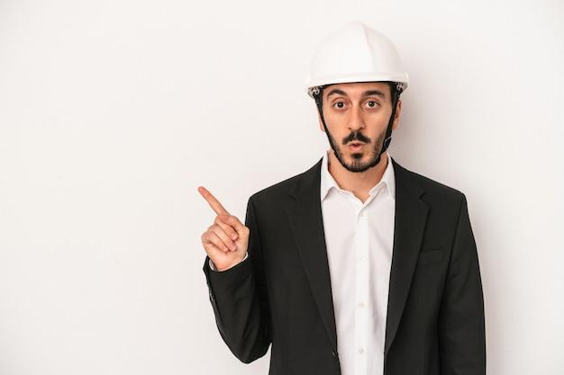 側面を指している白い背景で隔離の建設用ヘルメットを身に着けている若い建築家の男