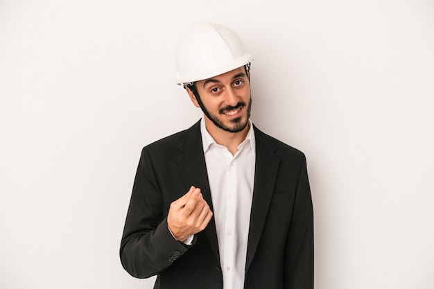 誘うようにあなたに指で指している白い背景に分離された建設用ヘルメットを身に着けている若い建築家の男が近づいています。