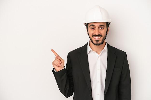 空白のスペースで何かを見せて、笑顔で脇を指して、白い背景で隔離の建設用ヘルメットを身に着けている若い建築家の男。