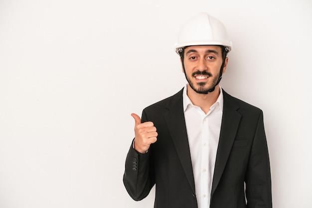 笑顔と親指を上げて白い背景で隔離の建設用ヘルメットを身に着けている若い建築家の男