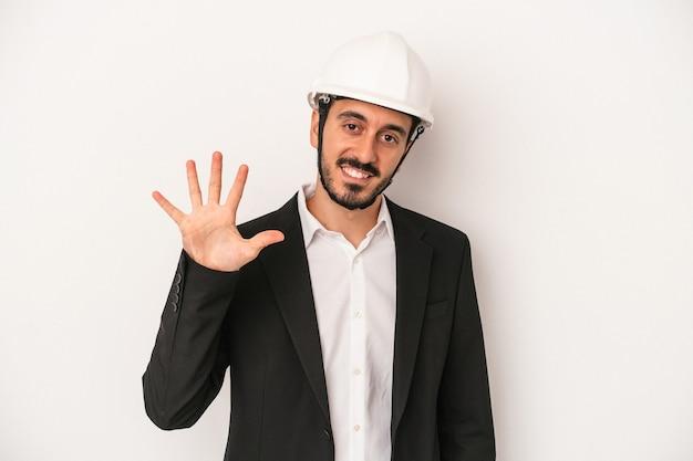 白い背景に分離された建設用ヘルメットを身に着けている若い建築家の男は、指で5番を示して陽気に笑っています。
