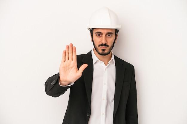 一時停止の標識を示す伸ばした手で立っている白い背景で隔離の建設用ヘルメットを身に着けている若い建築家の男は、あなたを防ぎます。