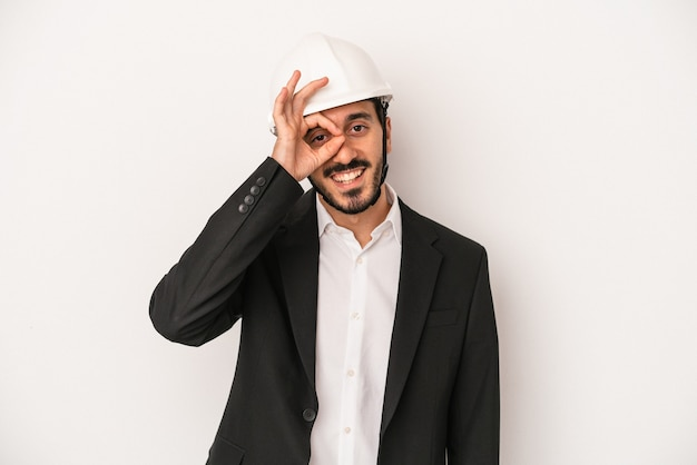 Young architect man wearing a construction helmet isolated on white background excited keeping ok gesture on eye.