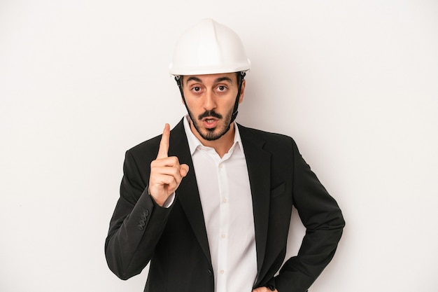 Young architect man wearing a construction helmet isolated on white background having an idea, inspiration concept.