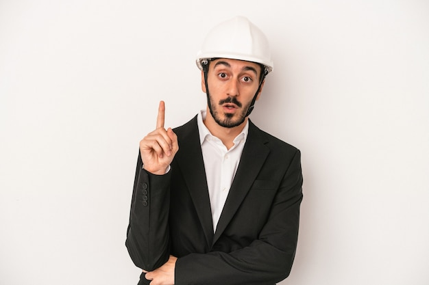 Young architect man wearing a construction helmet isolated on white background having some great idea, concept of creativity.