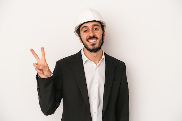 Young architect man wearing a construction helmet isolated on white background joyful and carefree showing a peace symbol with fingers.