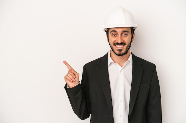 Young architect man wearing a construction helmet isolated on white background smiling and pointing aside, showing something at blank space.