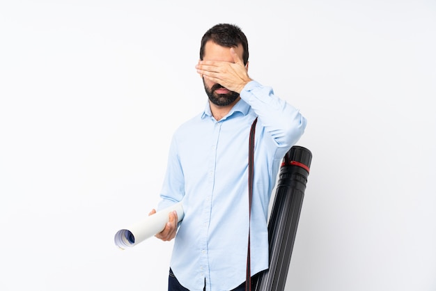 Young architect man with beard covering eyes by hands