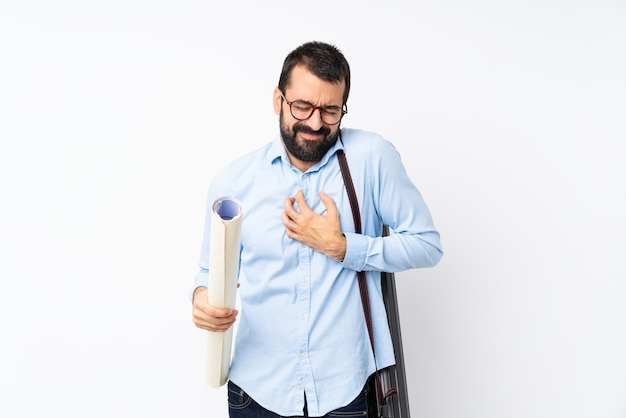 Young architect man with beard over isolated  having a pain in the heart