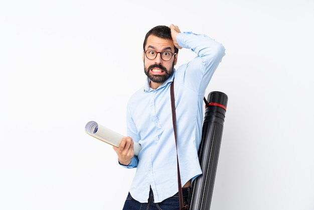 Young architect man with beard over isolated white frustrated and takes hands on head