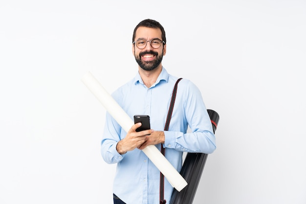 Young architect man with beard over isolated white  sending a message with the mobile
