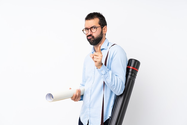Young architect man with beard over isolated white wall frustrated and pointing to the front