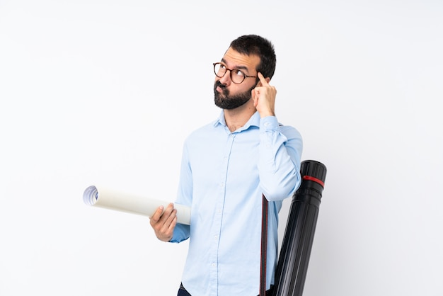 Young architect man with beard over isolated white wall having doubts and thinking