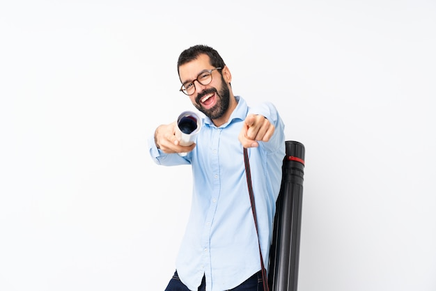 Young architect man with beard over isolated white wall points finger at you while smiling