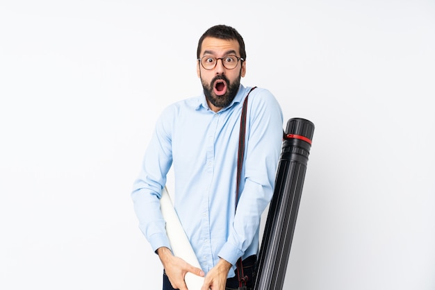 Young architect man with beard over isolated white wall with surprise facial expression