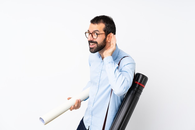 Young architect man with beard listening to something by putting hand on the ear