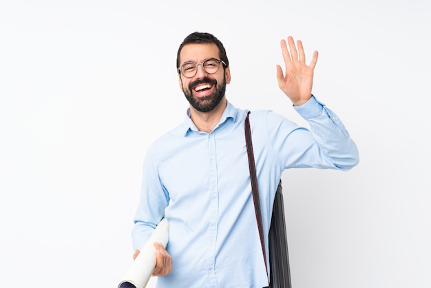Young architect man with beard saluting with hand with happy expression