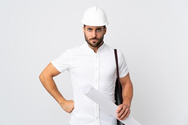 헬멧과 지주 청사진 흰색 화가에 고립 된 젊은 건축가 남자