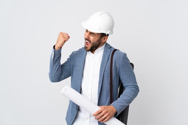 헬멧과 승리를 축하하는 흰색 배경에 고립 된 청사진을 들고 젊은 건축가 남자