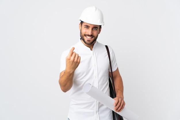 헬멧을 가진 젊은 건축가 남자와 오는 제스처를 하 고 흰색 배경에 고립 된 청사진을 들고