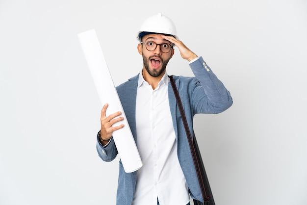 헬멧을 가진 젊은 건축가 남자와 측면을 보면서 깜짝 제스처를 하 고 흰색 배경에 고립 된 청사진을 들고