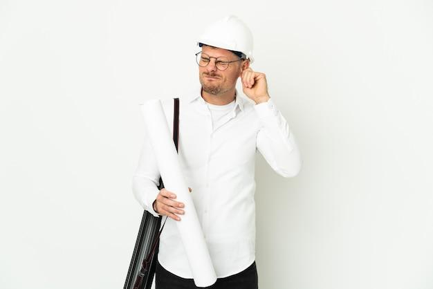 ヘルメットと白い背景で隔離の青写真を保持している若い建築家の男は欲求不満と耳を覆っている
