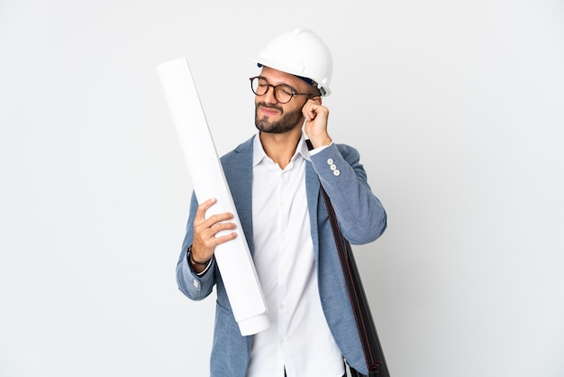 ヘルメットと白い背景で隔離の青写真を保持している若い建築家の男は欲求不満と耳を覆う