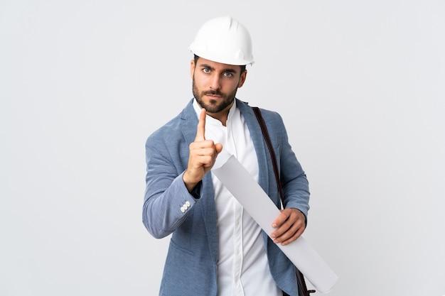 헬멧과 청사진을 들고 젊은 건축가 남자 좌절과 앞을 가리키는 흰색 배경에 고립 프리미엄 사진