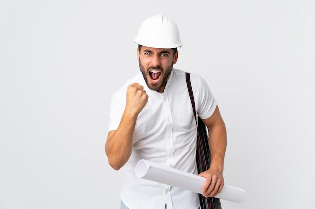 헬멧을 가진 젊은 건축가 남자와 나쁜 상황에 의해 좌절 흰색 배경에 고립 된 청사진을 들고