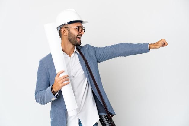ヘルメットと親指を立てるジェスチャーを与える白い背景で隔離の青写真を保持している若い建築家の男