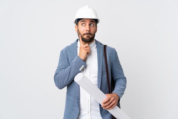 Молодой архитектор человек в шлеме и держит чертежи, изолированные на белом фоне, сомневаясь и думая
