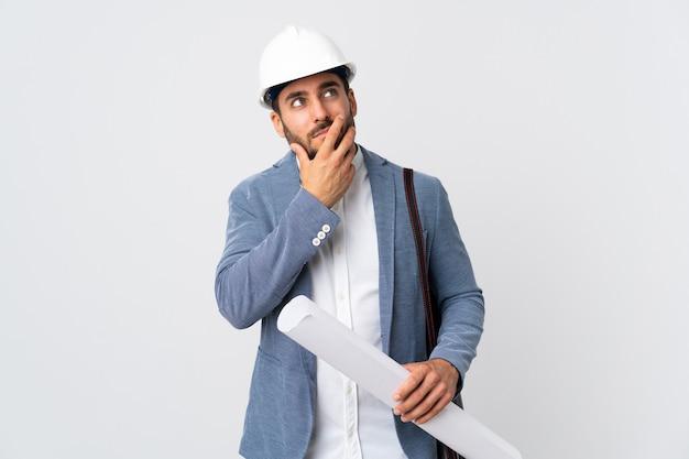 Молодой архитектор мужчина в шлеме и держит чертежи, изолированные на белом фоне, сомневаясь и с смущенным выражением лица