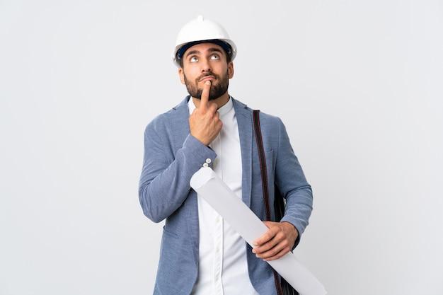 헬멧을 가진 젊은 건축가 남자와 찾는 동안 의심을 갖는 흰색 배경에 고립 청사진을 들고