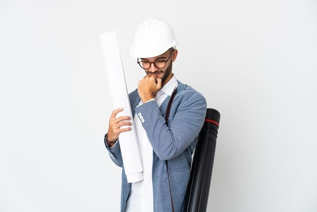 젊은 건축가 헬멧 남자와 의심을 갖는 흰색 배경에 고립 청사진을 들고
