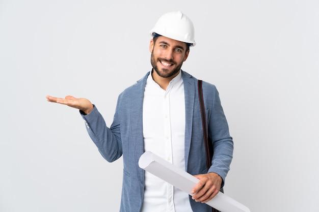 헬멧을 가진 젊은 건축가 남자와 광고를 삽입하는 손바닥에 가상 copyspace 들고 흰색 배경에 고립 된 청사진을 들고