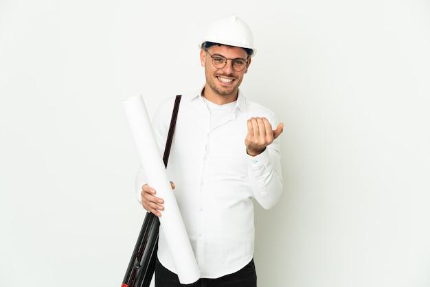 헬멧과 손으로와 서 초대 흰색 배경에 고립 된 청사진을 들고 젊은 건축가 남자. 와줘서 행복해