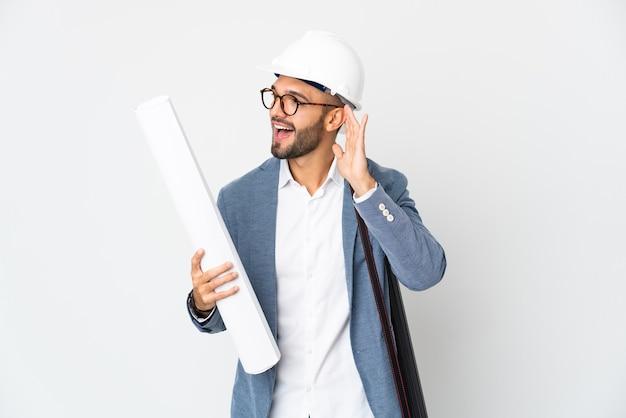 Молодой архитектор человек в шлеме и держит чертежи на белом фоне, слушая что-то, положив руку на ухо