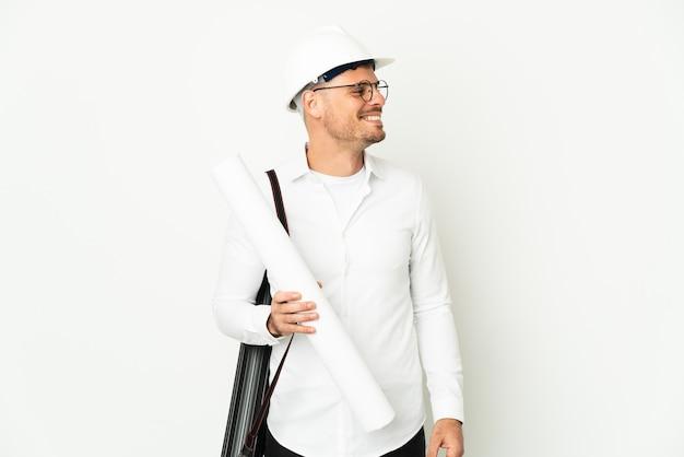 헬멧을 가진 젊은 건축가 남자와 측면을 찾고 흰색 배경에 고립 된 청사진을 들고
