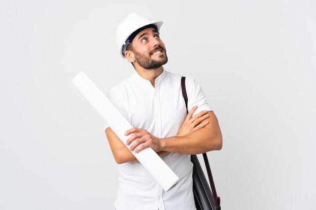 헬멧을 가진 젊은 건축가 남자와 웃는 동안 올려 흰색 배경에 고립 된 청사진을 들고