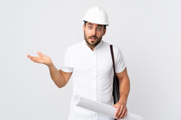 헬멧을 가진 젊은 건축가 남자와 의심 제스처를 만드는 흰색 배경에 고립 된 청사진을 들고