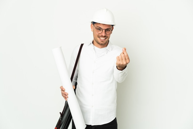 Молодой архитектор человек в шлеме и держит чертежи, изолированные на белом фоне, делая денежный жест