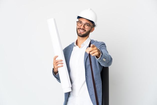 헬멧을 가진 젊은 건축가 남자와 행복 한 표정으로 앞을 가리키는 흰색 배경에 고립 된 청사진을 들고