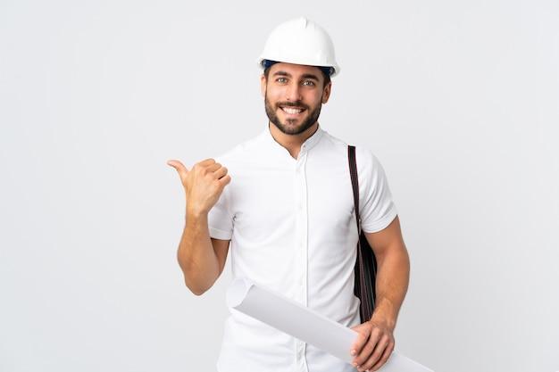 헬멧 및 제품을 제시하기 위해 측면을 가리키는 흰색 배경에 고립 청사진을 들고 젊은 건축가 남자