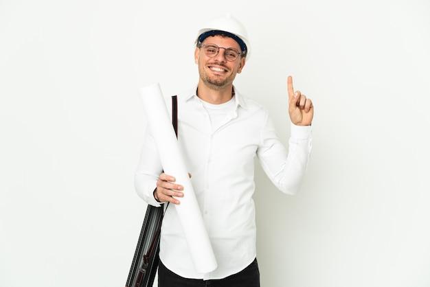 Молодой архитектор мужчина в шлеме и держит чертежи на белом фоне, указывая на отличную идею