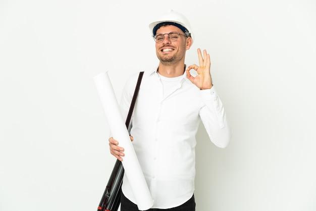 헬멧과 손가락으로 확인 표시를 보여주는 흰색 배경에 고립 청사진을 들고 젊은 건축가 남자