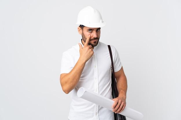 헬멧과 뭔가 보여주는 흰색 배경에 고립 된 청사진을 들고 젊은 건축가 남자